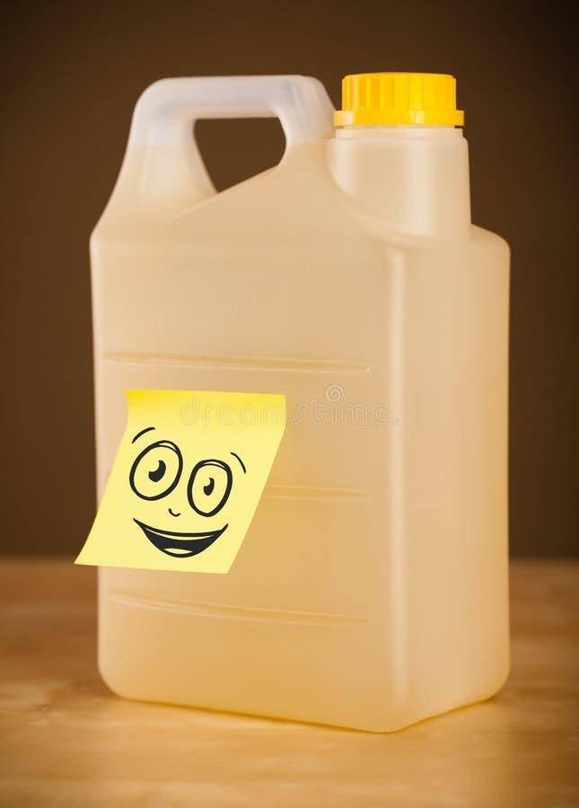 De post-itnota met smileygezicht sticked op gallon stock foto's