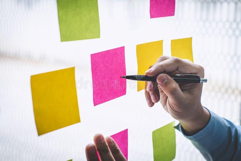 De post-itnota's van het zakenmangebruik aan de planning van idee en bedrijfs marketing strategie, Kleverige nota op glasmuur stock afbeelding