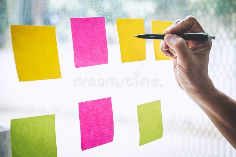 De post-itnota's van het zakenmangebruik aan de planning van idee en bedrijfs marketing strategie, Kleverige nota op glasmuur royalty-vrije stock foto's