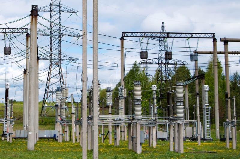 De post van de elektriciteitsdistributie Veel draden, polen en schilden stock afbeeldingen