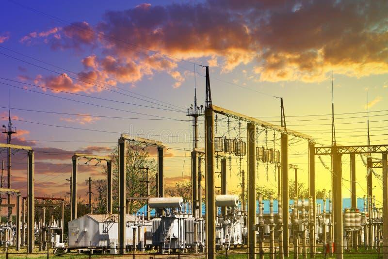 De post van de hoogspannings stroom - elektrische polen en lijnen op achtergrond van de zonsopgang de gele bewolkte hemel royalty-vrije stock afbeeldingen