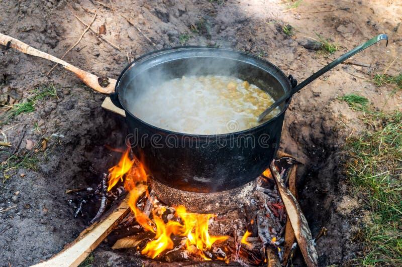 De pot met voedsel is gekookt op een open brand stock afbeelding
