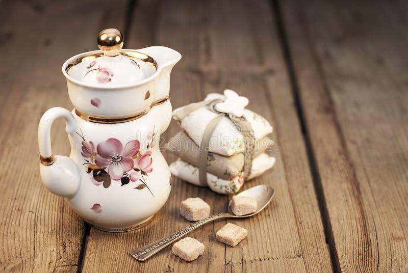 De pot van de porseleinthee en zilveren lepel met suiker stock fotografie