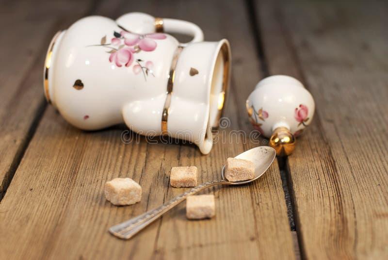 De pot van de porseleinthee met suikerkubussen en met de hand gemaakte hoofdkussens stock foto's