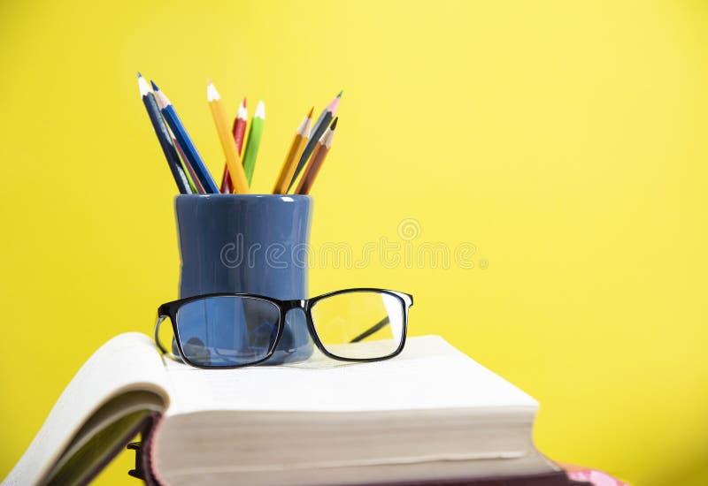 De potloden kleuren in een potloodgeval en glazen op een boek in concept van het bibliotheek het gele onderwijs terug naar school royalty-vrije stock fotografie