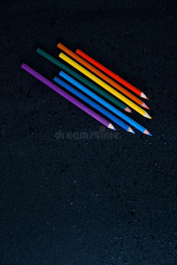 De potloden van de regenboogkleur op een zwarte achtergrond met dalingen van water stock fotografie
