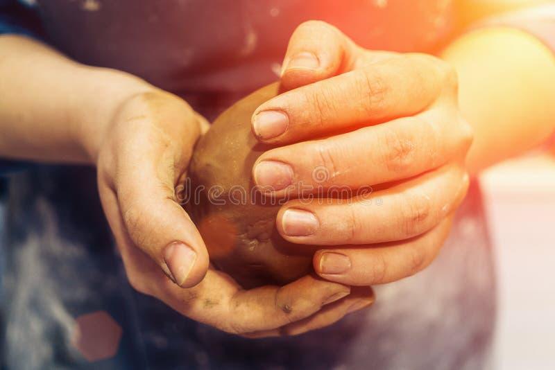 De pottenbakker houdt klei in handen en kneedt het stock afbeeldingen