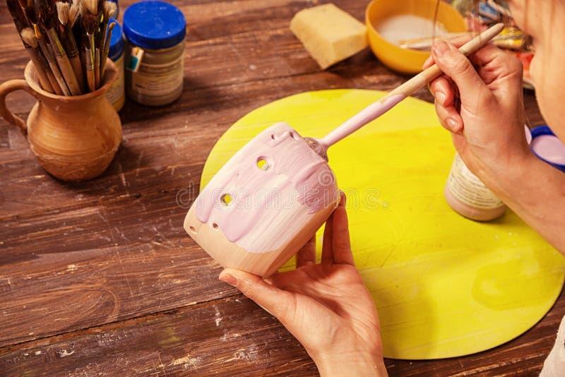 De pottenbakker schildert een klei stock afbeeldingen