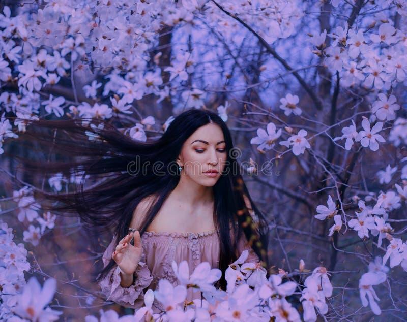 De prachtige aantrekkelijke donker-haired dame met ogen sloot tribunes in de tuin van bloeiende magnolia's haarvliegen omhoog met stock foto