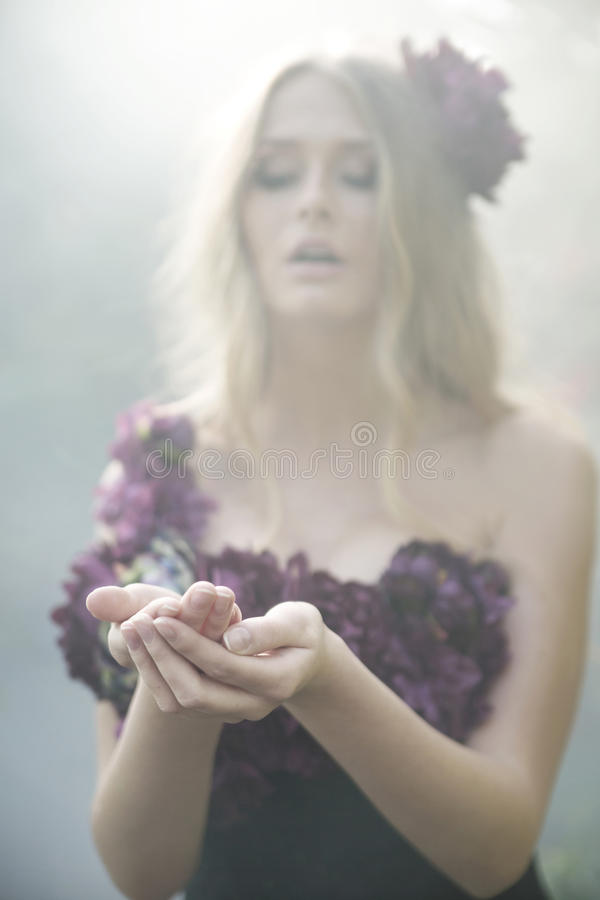 De prachtige blonde vrouw kleedde zich in bloemrijke kleren stock afbeeldingen