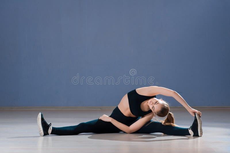 de praktijk van de yogavrouw in een opleidingszaal stock foto