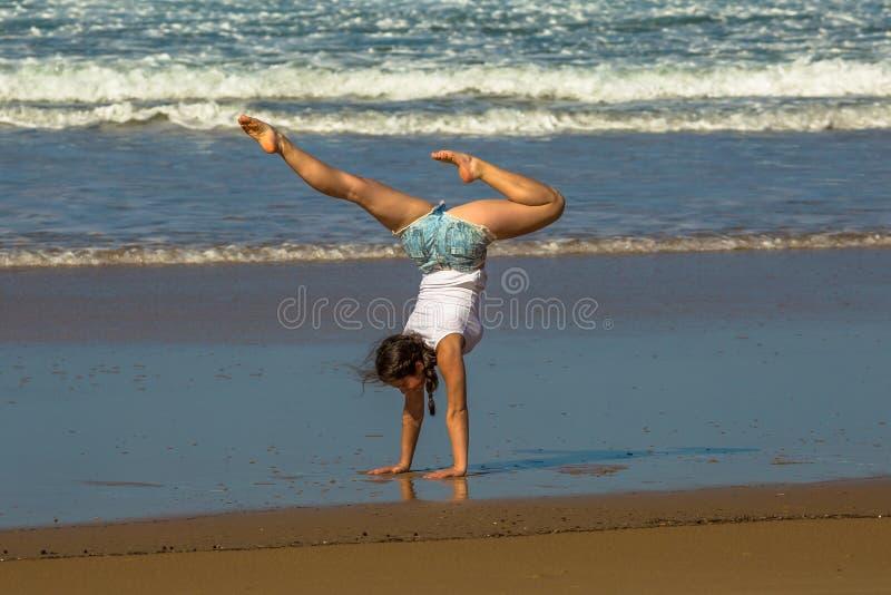 De praktijkyoga van de turnervrouw op het strand stock foto