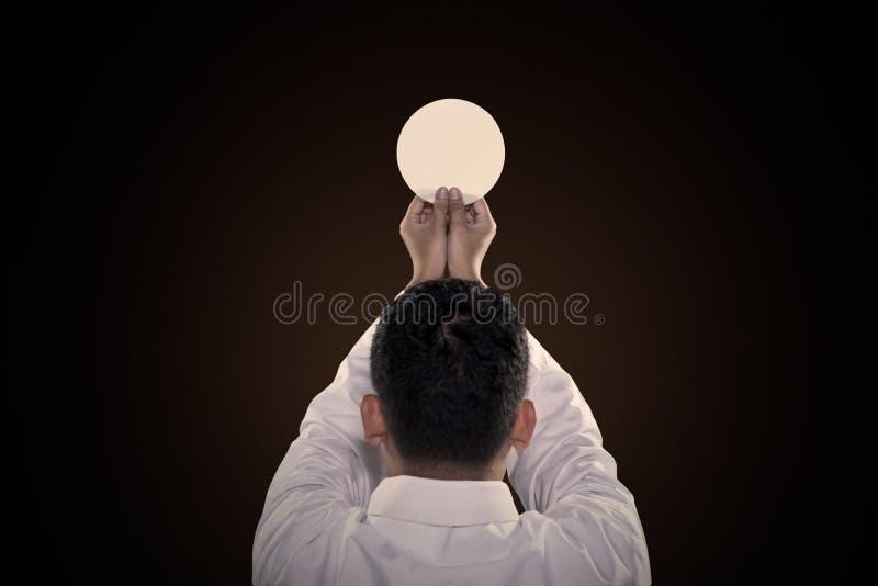De predikant bidt aan Godswijding een brood stock foto's