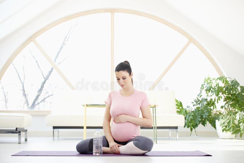 De Pregnanvrouw in yoga stelt stock afbeeldingen