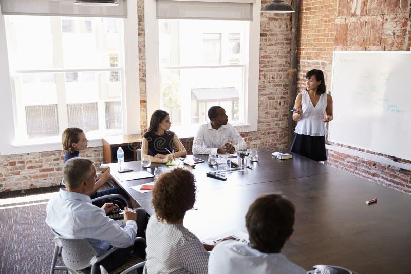 De Presentatie van onderneemsterat whiteboard giving in Bestuurskamer royalty-vrije stock afbeelding