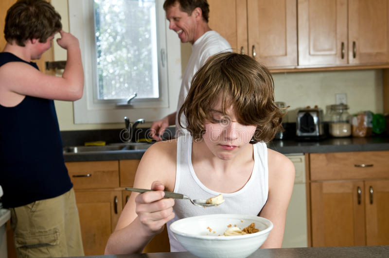 De pret van het familieontbijt - tienerbroers die graangewas hebben: spontane schoten royalty-vrije stock foto