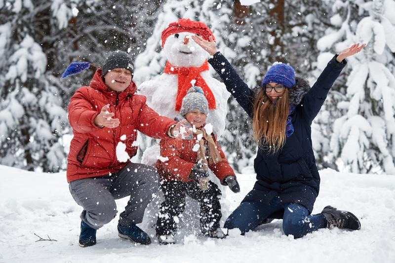 De pret van de winter een meisje, een mens en een jongen die een sneeuwman maken royalty-vrije stock fotografie