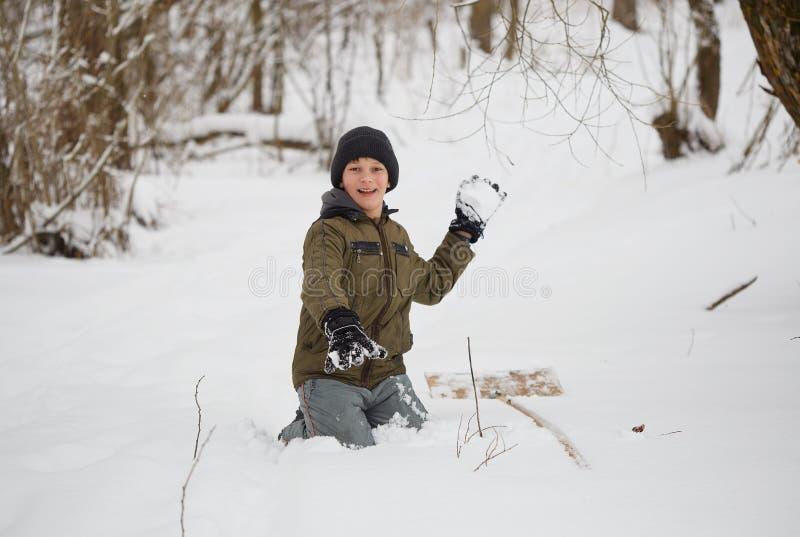 De pret van de winter tiener die pret het spelen met sneeuw hebben stock afbeelding
