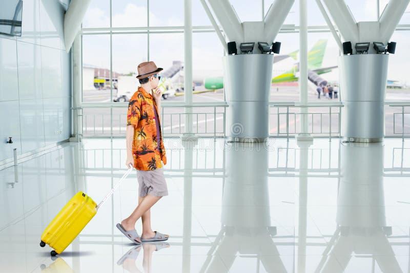 De Preteenjongen draagt een bagage in de luchthaventerminal stock afbeelding