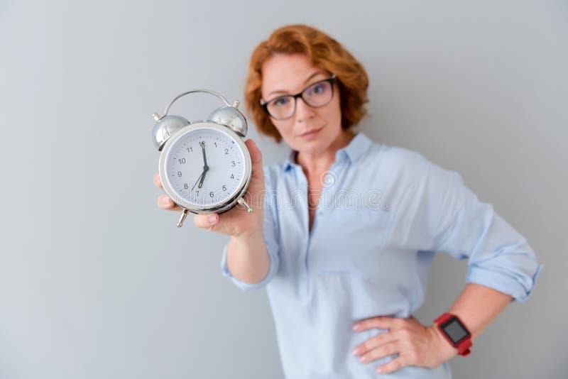 De prettige ernstige wekker van de vrouwenholding stock fotografie