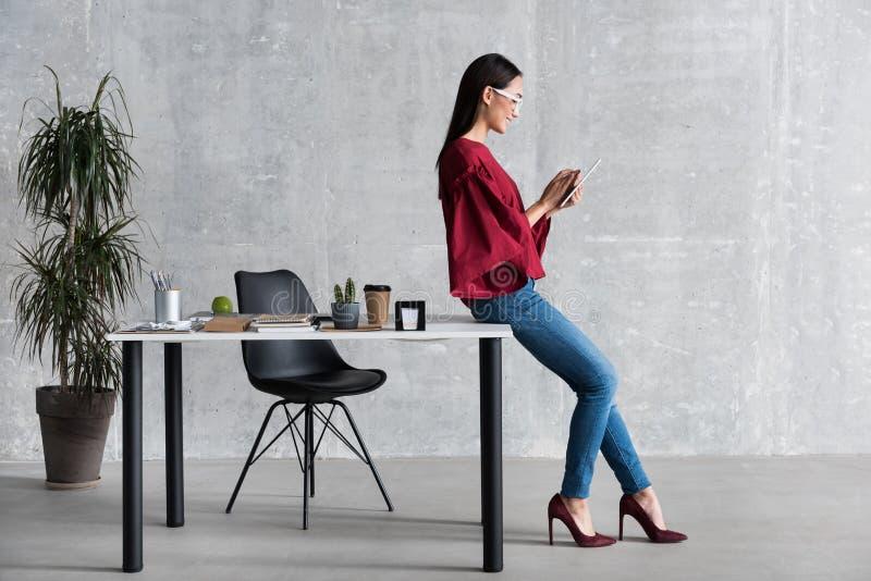 De prettige fascinerende bedrijfsvrouw houdt slim gadget royalty-vrije stock afbeeldingen