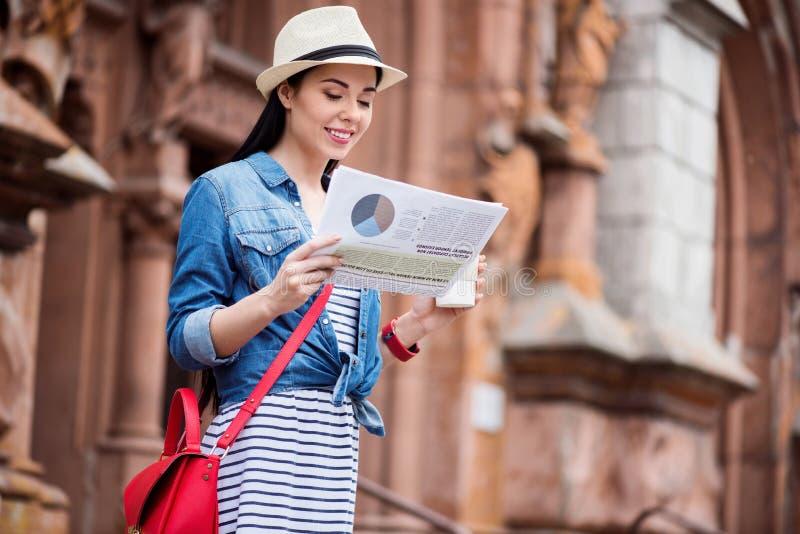 De prettige het glimlachen krant van de vrouwenlezing stock afbeeldingen