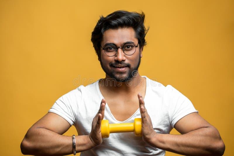 De prettige Indische sportman doet exercies voor borst en borst stock afbeelding