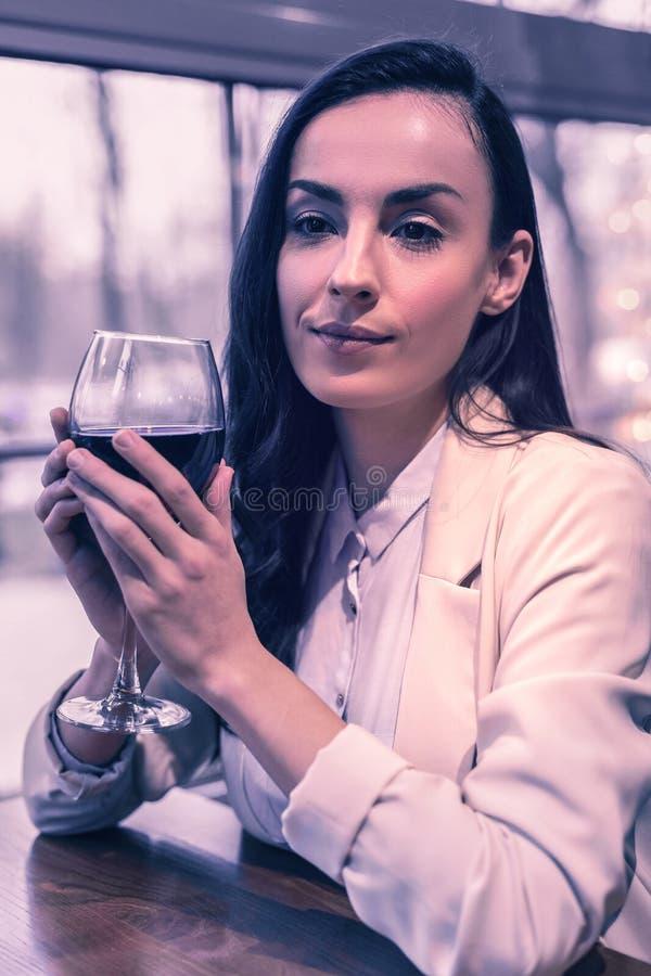De prettige jonge vrouw die van Nice rode wijn drinken stock foto