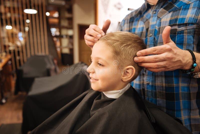 De prettige kapper die van Nice het jongenshoofd houden stock foto's