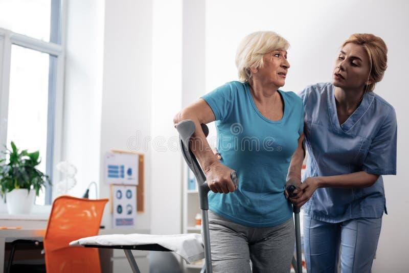 De prettige verpleegster die van Nice haar patiënten helpen te lopen stock afbeeldingen