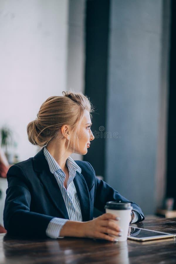 De prettige vrouw wacht op haar partner bij de koffie stock afbeelding