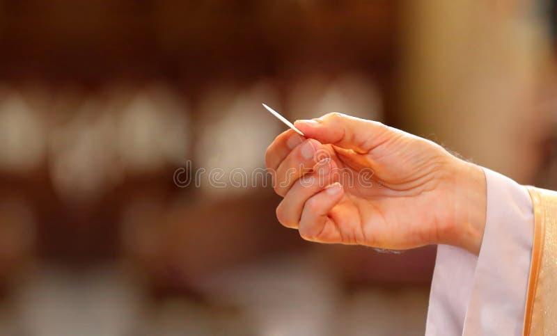 De priester geeft heilige kerkgemeenschap aan gelovig stock fotografie