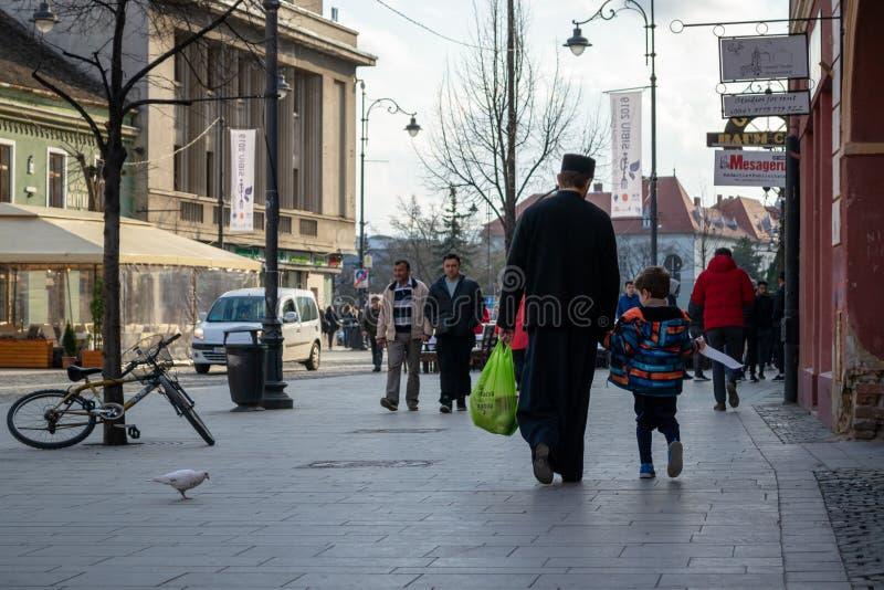 De priester kleedde zich in het zwarte lopen, het houden van een childshand en het dragen van een zak met kruidenierswinkels stock foto's