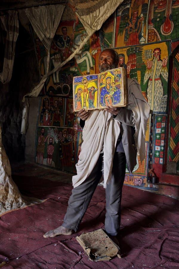 De priester opent een geïllustreerde Bijbel binnen een kerk in Ethiopië stock afbeeldingen