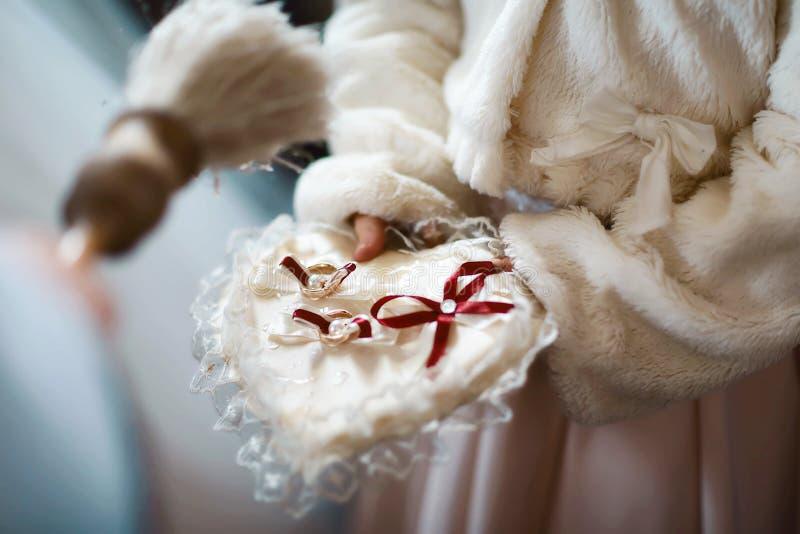 De priester zegent huwelijks gouden ringen met heilig water in de kerk stock afbeelding