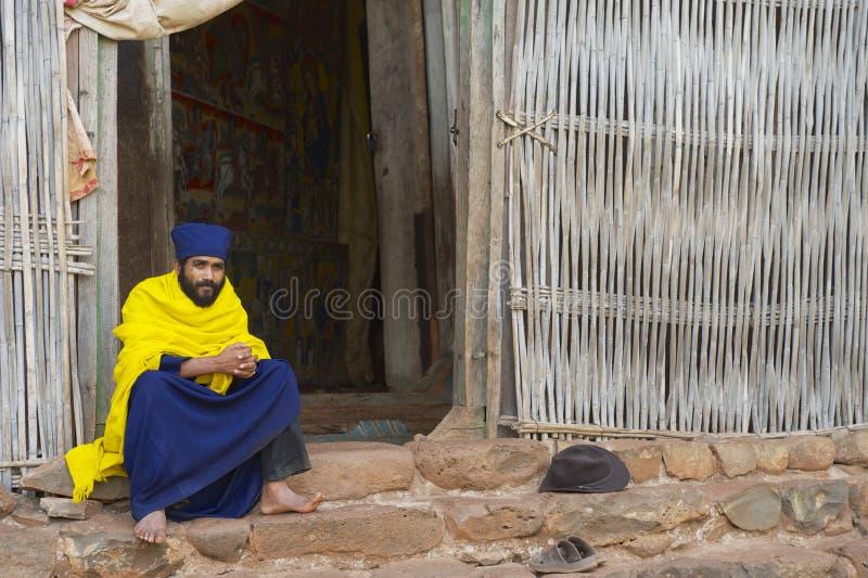 De priester zit bij de ingang aan de oude kerk Ura Kidane Mehret in Bahir Dar, Ethiopië stock foto's