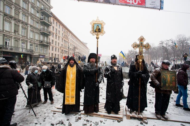 De priesters van Oekraïense Orthodoxe Kerk bevinden zich bij voorzijde van barricades op de straat van de sneeuwwinter tijdens ant royalty-vrije stock foto's