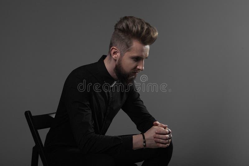 De priesterzitting op een stoel vouwde zijn handen met het dwars bidden op een grijze achtergrond royalty-vrije stock afbeeldingen