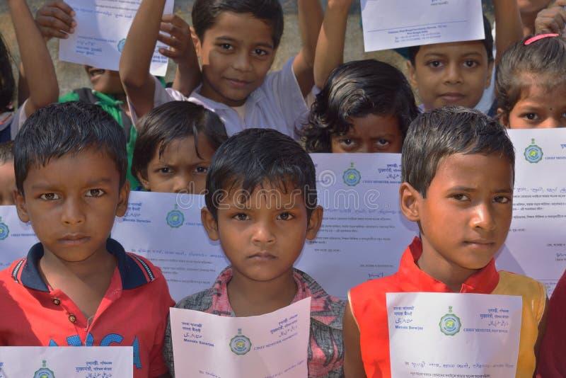 De primaire studenten toont hun groetenbrieven die door de Belangrijkste minister van West-Bengalen naar hen werden verzonden stock foto