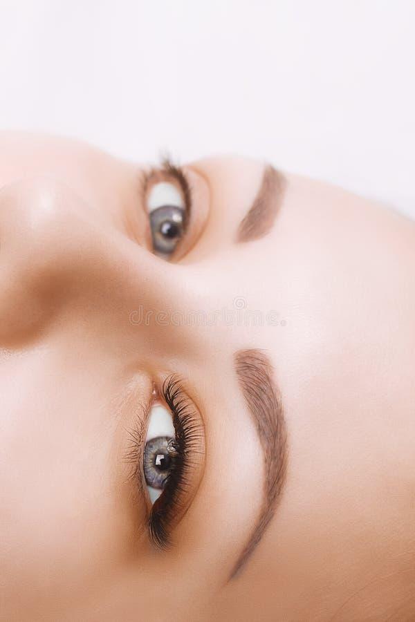 De Procedure van de wimperuitbreiding Het oog van de vrouw met lange wimpers Sluit omhoog, selectieve nadruk royalty-vrije stock afbeeldingen