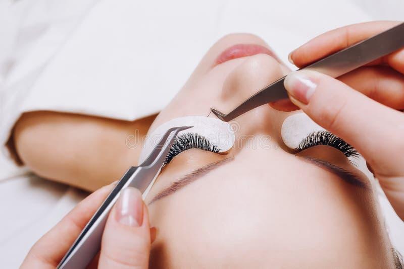De Procedure van de wimperuitbreiding Het oog van de vrouw met lange wimpers Sluit omhoog, selectieve nadruk stock fotografie