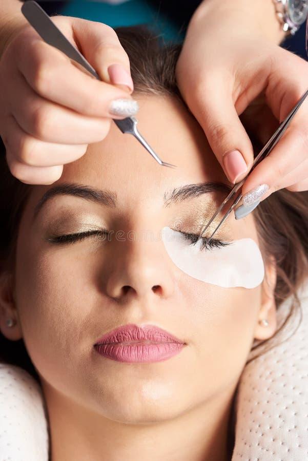 De Procedure van de wimperuitbreiding De schoonheidsspecialist van close-uphanden met pincet in handen stock afbeeldingen