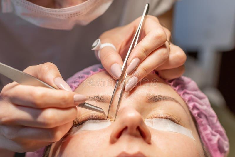 De Procedure van de wimperuitbreiding Vrouwelijk oog met lange wimpers Wimpers, close-up, selectieve nadruk stock afbeeldingen