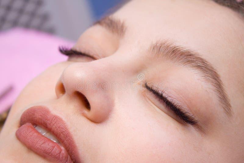 De Procedure van de wimperuitbreiding Vrouwengezicht met Lange valse Wimpers Sluit omhoog macro van manierogen visagein wordt ges royalty-vrije stock afbeelding