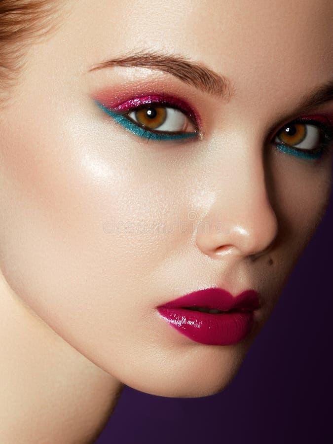 De producten van schoonheidsmiddelen op exhibition Sluit omhoog van vrolijke jonge vrouw met kleurrijke make-up Schoonheidsportre royalty-vrije stock foto