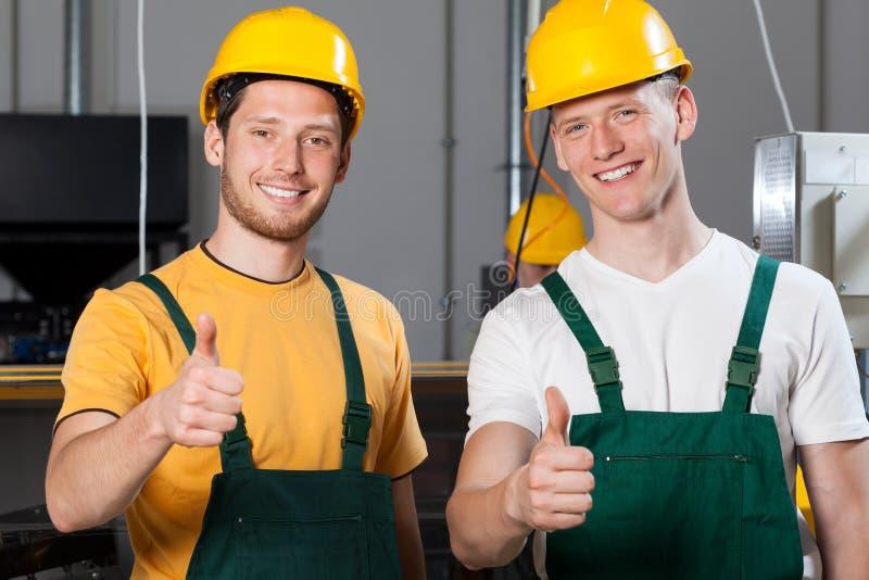De productiearbeiders die duimen tonen ondertekenen omhoog stock fotografie