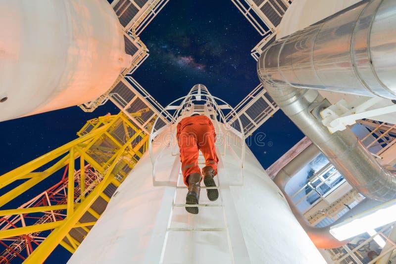 De productieingenieur beklimt tot bovenkant onder druk zet schip te controleren en het proces van het dehydratiegas in nachtploeg stock afbeeldingen