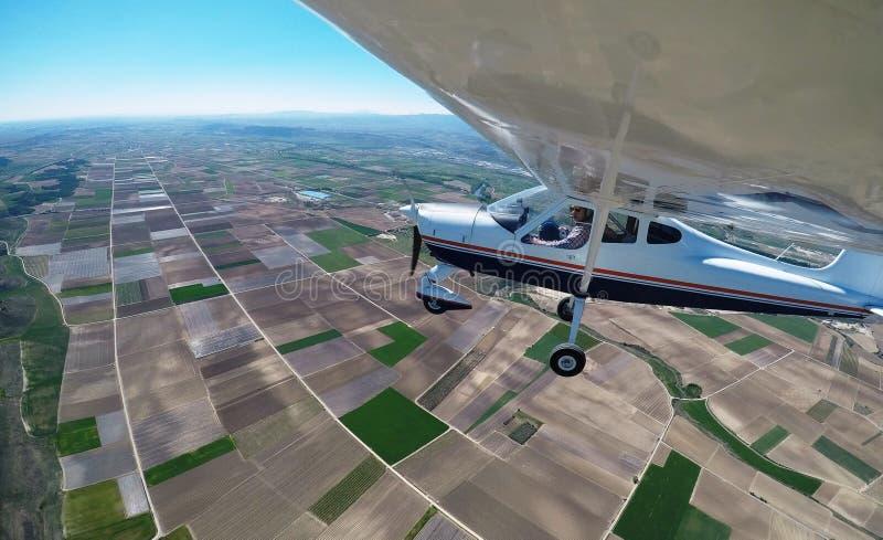 DE PROEF VLIEGENDE OVER LANDBOUWGRONDEN MET EEN VLIEGTUIG KIEZEN MOTORIGE EN HOGE VLEUGELvliegtuigen uit royalty-vrije stock afbeeldingen