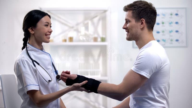 De professionele arts het bevestigen steun van de titaanpols, die aan mannelijke patiënt, kliniek glimlachen royalty-vrije stock fotografie