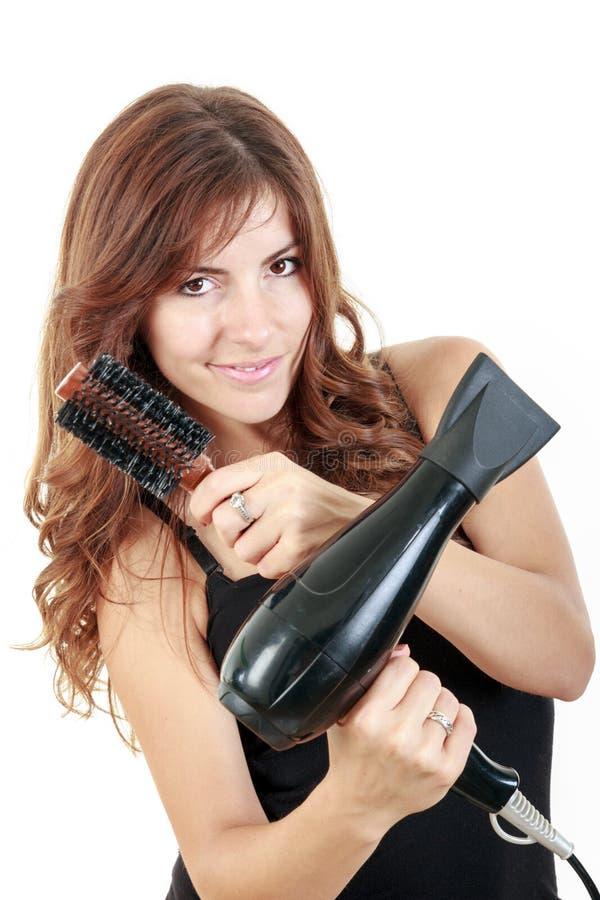 De professionele borstels van de kapperholding en hairdryer het glimlachen royalty-vrije stock foto's